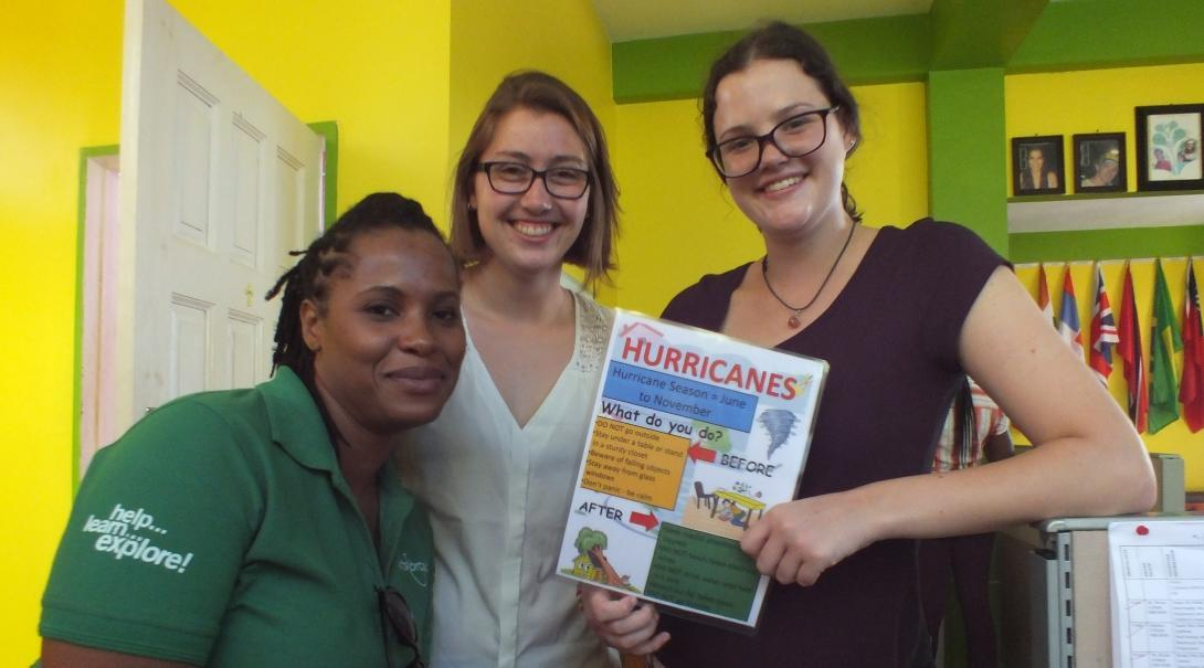 Female International Development interns pose in a day centre holding a poster during their Disaster Management work experience in Jamaica.